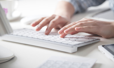 Hands typing on computer keyboard in office desk.