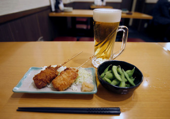"""Typical combination of beer, deep fried meat on skewers and green soybeans are seen on a table at """"Ikken me sakaba"""", a discount izakaya bar offering cheap food and drinks, in Tokyo"""