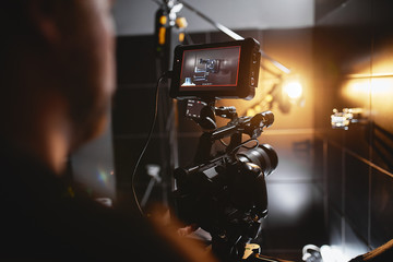 Fototapeta Video production backstage. Behind the scenes of creating video content, a professional team of cameramen with a director filming commercial ads. Video content creation, video creation industry. Low obraz