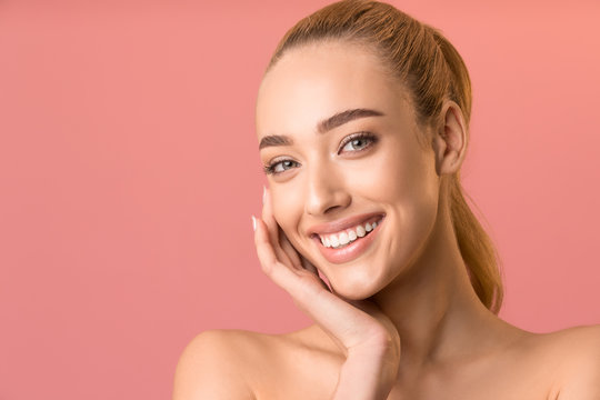 Attractive Woman Touching Face Smiling To Camera Over Pink Background