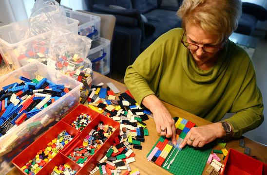 "Rita Ebel, nicknamed ""Lego grandma"", builds a wheelchair ramp from donated Lego bricks in the living room of her flat in Hanau"