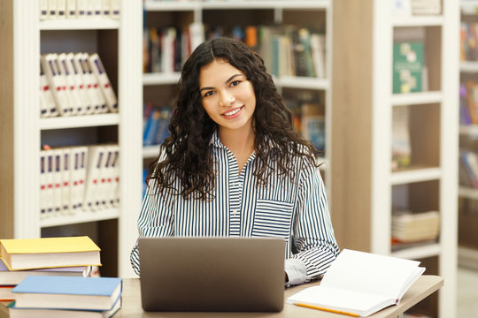 Confident latina girl using laptop in modern library