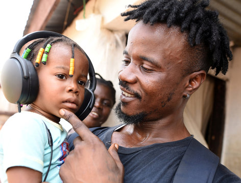 Yousef Kamara holds his daughter Stylvia in front of their house in Freetown,