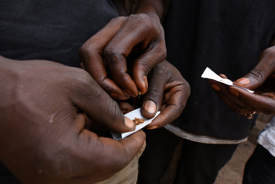 Members of the Freetown street gang Giverdam Gaza roll joints in front of the gang's headquarters in Freetown,