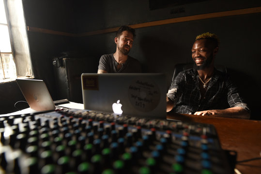 British folk singer Frank Turner discusses music production with Sierra Leonean producer Solo while the pair volunteer at the Way Out media studio in Freetown