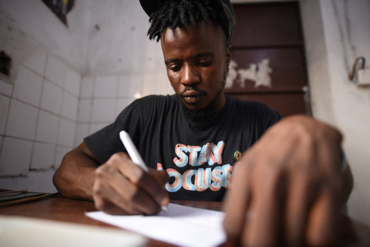 """Yousef Kamara works on a poem in the Way Out media center's """"Writer's Room"""" in Freetown"""