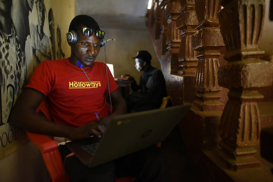 A Way Out member Milton Kanu edits a video under their center in Freetown