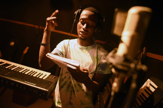 A Way Out member records a vocal track in the center's recording studio in Freetown