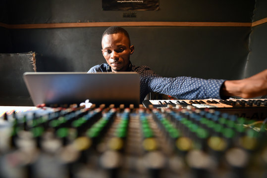 Gibrilla Kamara, Way Out's office manager, mixes tracks in the media center's recording studio in Freetown