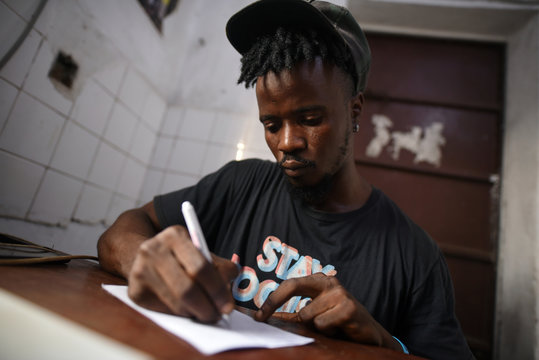 """Yousef Kamara works on a poem in the Way Out media center's """"Writers Room"""" in Freetown,"""