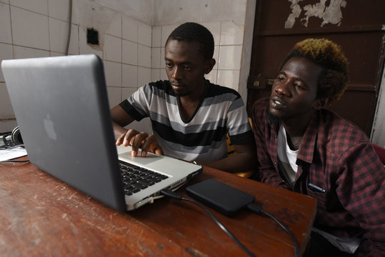 """Way Out members Foday Sillah and Ibrahim Dumbuya edit video footage at the centre's """"Writer's Room"""" in Freetown"""