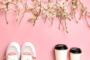 Female Fashionable Sneakers, Coffee or tea paper cup and spring branches of white flowers on pink background top view flat lay. Take away coffee cup, mockup. Creative spring background, lifestyle Wall mural