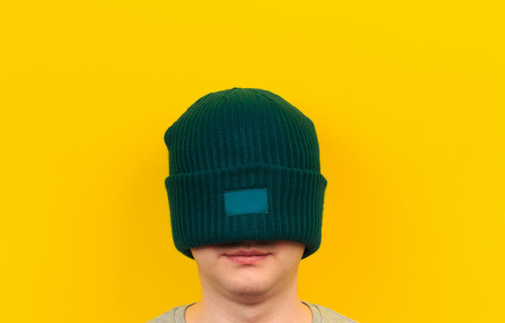 head of a man wearing colorful beanie hat on yellow background  - Image
