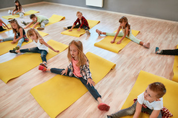 Warming up. Group of children sitting on the floor and doing gymnastic exercises in the dance studio. Physical education