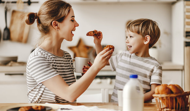 preparation of family breakfast. mother and child son cut bread  and eat cookies with milk in morning.