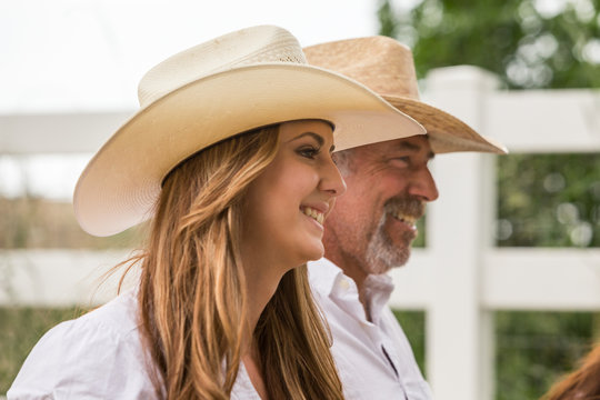 Profile of smiling cowgirl and her father. Bridger, Montana, USA