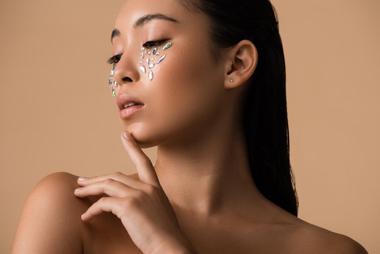 beautiful naked asian girl with rhinestones on face isolated on beige