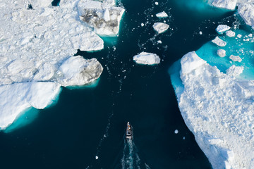 Aerial view of Small boat making a way through icebergs in Greenland