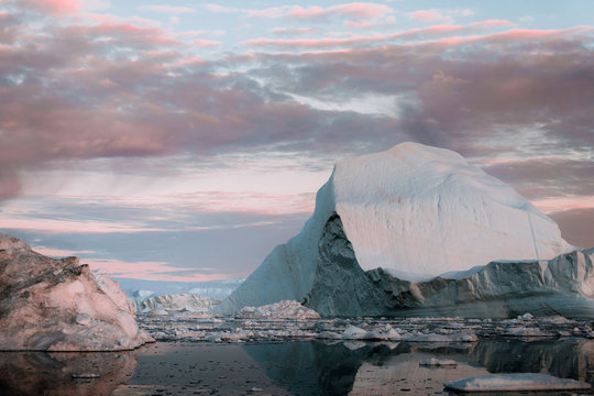 Sunset sky coloring icebergs in the arctic ocean