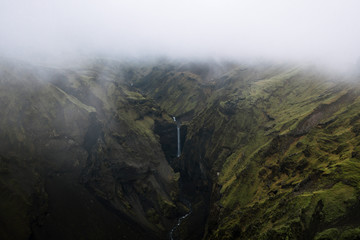Aerial view of waterfall in the icelandic mountains with low clouds