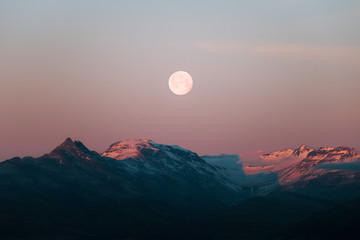 Moon rising over mountains during a dramatic sunset in Iceland