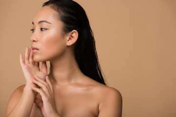 beautiful naked asian girl  looking away and touching face isolated on beige
