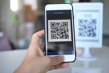 Women's hand uses a mobile phone application to scan QR codes in stores that accept digital payments without money and plastic tags on the table. QR code payment and cash technology concept