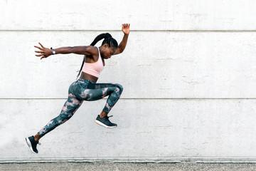 African-American athlete sprinter jumping