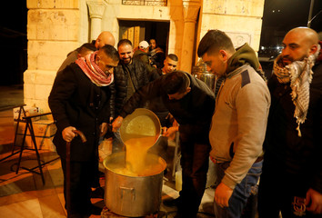 Palestinians prepare lentil soup for worshippers who perform the Fajr (Dawn) prayers, outside Al-Nasir mosque in Nablus, in the Israeli-occupied West Bank