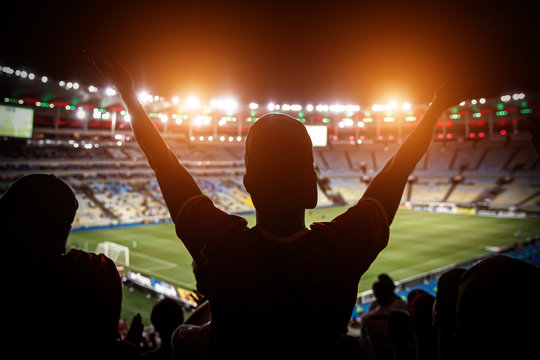 Football fans support team on crowded soccer stadium.