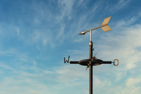 Old rusty weather vane against a cloudy blue sky