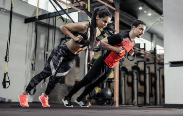 Sport. Man and Women training with fitness straps in the gym. Beautiful lady exercising her muscles...