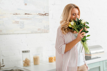 happy woman smelling bouquet of tulips at home