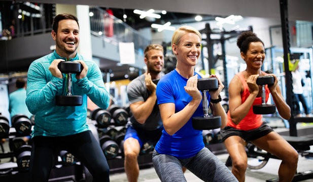 Group of young happy fit people doing exercises in gym