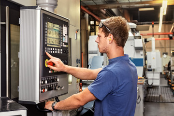 Skilled worker controlling a digitally programmed machine tool Fotomurales