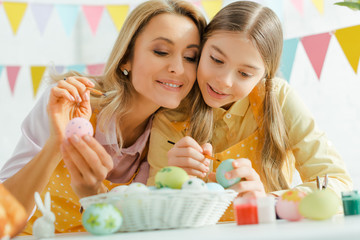 selective focus of happy daughter and mother painting easter eggs near decorative bunnies