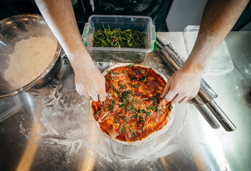 Closeup hand of chef baker in black uniform making pizza at kitchen Wall mural
