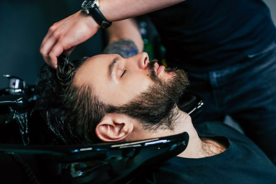 Clean hair.  Side view photo of a young relaxed handsome man washing his hair in a barbershop.