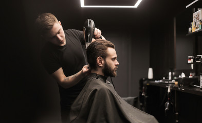 Special day. Side view low angled photo of a barber stylist, who is drying hair of his client, using a special round comb.