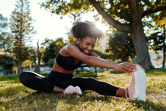 Smiling portrait of an sporty fit african american young woman sitting on lawn stretching her legs in the park - happy young black woman warming up her muslces before running