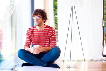 Relaxed young man enjoying his morning tea at home