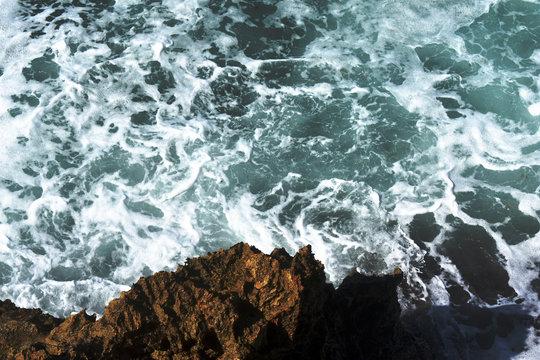 ocean waves crash against rocks