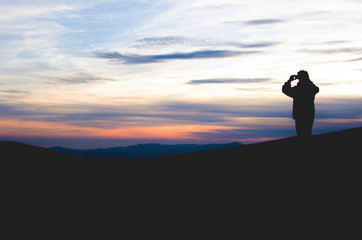 Keuken foto achterwand Candy roze man on top making a photo of mountain landscape at sunset