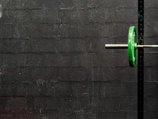 Green barbells on black background - sport concept