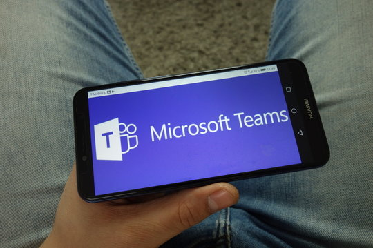 KONSKIE, POLAND - April 13, 2019: Man holding smartphone with Microsoft Teams communications platform logo