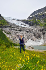 The young girl looks at the Boyabreen glacier, which is the sleeve of large Jostedalsbreen glacier and wild yellow flowers in the foreground. Melting glacier forms the lake with clear water. Norway.