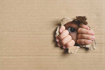 Little girl peeking from a hole on cardboard box. Concept of a human trafficking, Spying and Curiosity