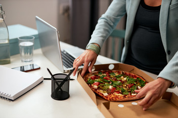 Cutout picture of caucasian pregnant business woman in forties and dressed in suit standing in office and having pizza for lunch.