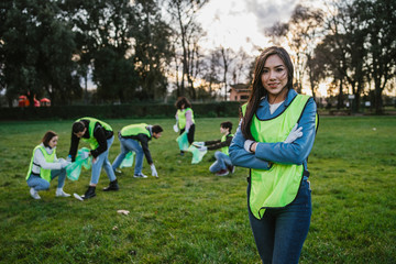 Group of friends at volunteer garbage collection event in a park - Millennial having fun together - Happy people cleaning area with bags - Ecology concept - Portrait of the leader in the public event
