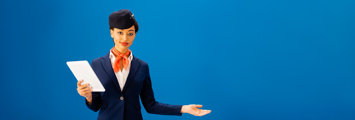 panoramic shot of smiling african american flight attendant holding digital tablet and pointing with hand isolated on blue